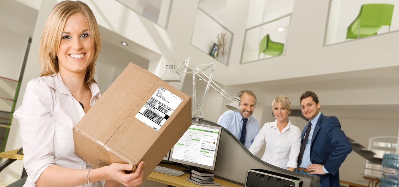 Mailing Support image of a woman in the foreground holding a package with coworkers behind her and a mailing machine in between them.